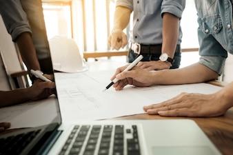 建築家のエンジニアは、青写真とテーブルで議論 - 手とプロジェクトの印刷物の拡大