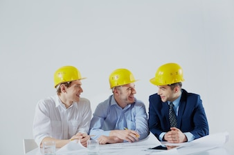 Architects with yellow helmets laughing