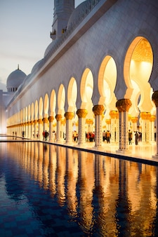 Archs of Shekh Zayed Grand Mosque reflect in the water before it