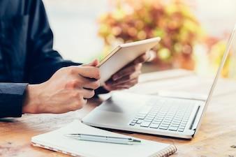 Азии человек, используя планшет и ноутбук на столе в кафе с винтажным тонированным фильтром.