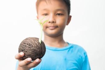 Asian boy holding baby head plant