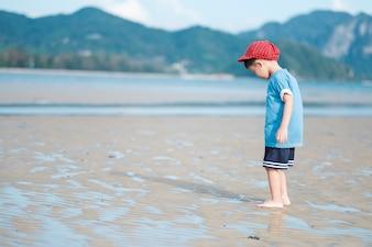Азиатский мальчик, идущий на пляже на открытом воздухе Море и голубое небо