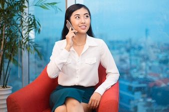 Asian Business Lady Talking on Phone in Armchair