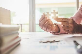 アジアのビジネスウーマンは木製のオフィスデスクでパズルを選ぶ。ビジネスソリューションの成功と戦略のコンセプト。ジグソーパズルを接続しているビジネスマンの手。選択フォーカスの写真を閉じます。