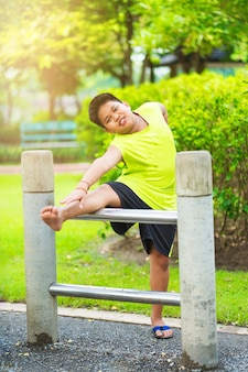 Asian sport boy stretching on iron bar in garden