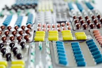 Assorted pharmaceutical medicine pills, tablets and capsules on the table.