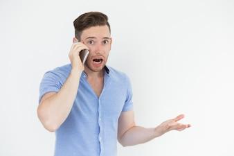 驚いたハンサムな男が電話で話す