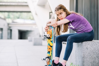 Athletic girl is leaning on her colorful skateboard