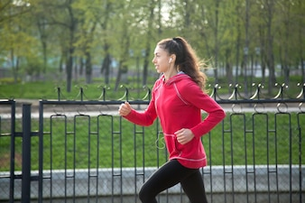 Attractive cheerful woman running in park