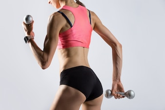 Attractive fit woman working out with dumbbells. Rear view