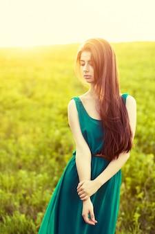 日没の緑のドレスでポーズ魅力的な女の子