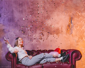 Attractive girl with champagne and confetti
