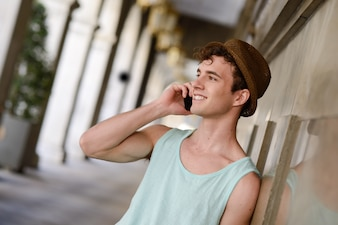 Attractive guy with hat talking on phone