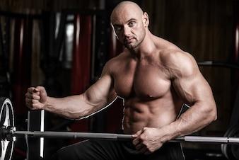 魅力的な筋肉のボディービルダーの男は、ジムでバーベルでエクササイズをする準備ができています。ガイのボディービルダーはジムで疲れました。エクササイズ後にジムで休む若い男のボディービルダー
