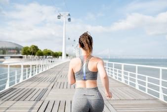 魅力的なスポーティーな女性ジョギング橋で
