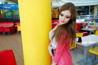 Attractive teenager posing next to a yellow column