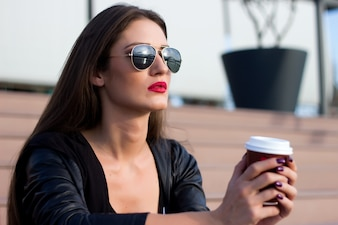 コーヒーを飲んで階段に座っている魅力的な女性