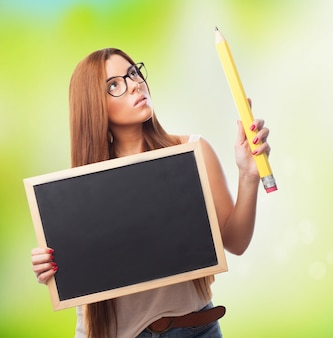 Attractive woman in spectacles with blackboard and big pencil