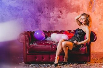 Attractive woman posing on couch with balloons