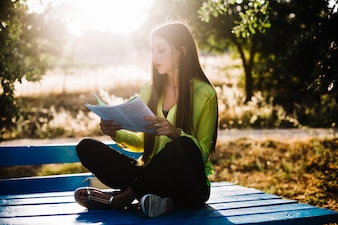 Attractive woman with papers in park