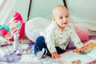 Baby boy touching book looking away