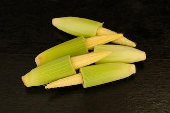 Baby corn on black wooden background