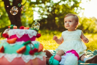 Baby in a park looking at soap bubbles