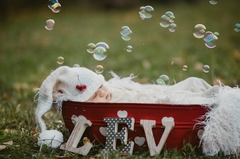 Baby sleeping in a basket on the lawn with soap bubbles