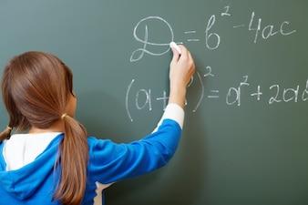 Back view of girl writing on a blackboard
