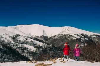 Back view of two young women friends on the background of snowy mountains, sunny winter day outdoors.
