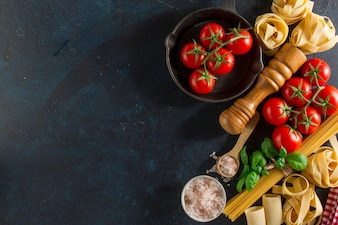 Background with fresh tomatoes and variety of pasta