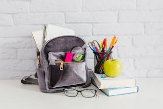Backpack, books, apple and glasses