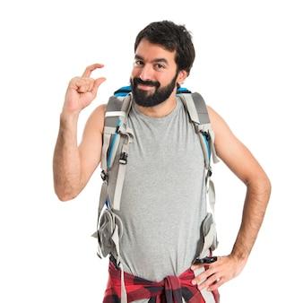 Backpacker doing tiny sign over white background