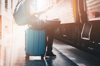 旅行者と一緒に駅のスマートフォンから音楽を聞くバックパッカー。旅行のコンセプト。
