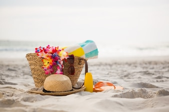 Bag with beach accessories kept on sand