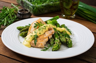 Baked chicken garnished with asparagus and herbs