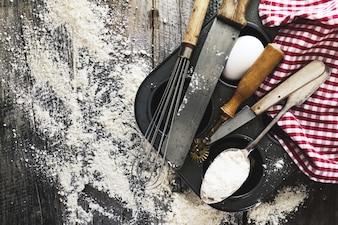 ベーキングコンセプトキッチンは、小麦粉と木製の背景に焼くためのカトラリーアクセサリー。上面図。クッキングプロセス。誰も。