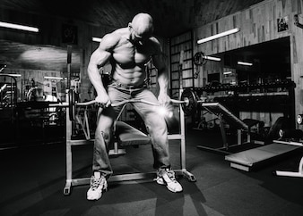 Bald man in jeans lifting heavy barbell