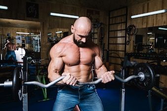 Bald man lifting barbell during trainin