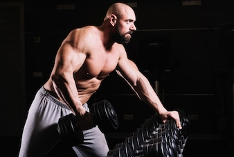 Bald man with dumbbell near rack