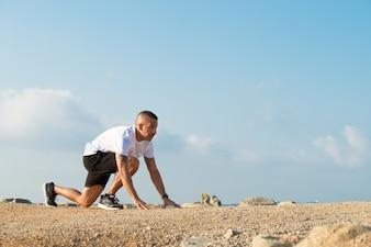 Лысый молодой спортсмен готовится к марафону