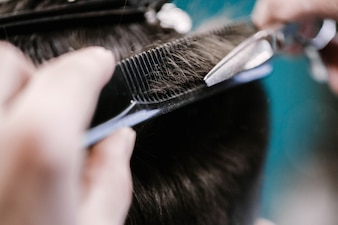 Barber cuts man's hair with scissors