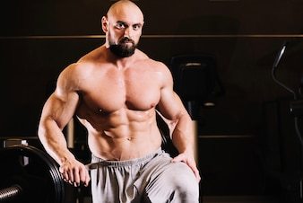 Bare-chested man posing near barbell