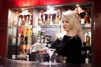 Bartender girl serving martini