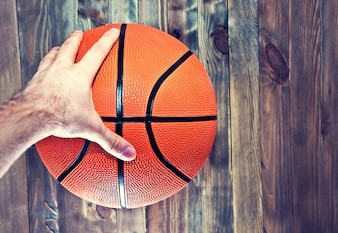 Basketball ball on wooden hardwood floor grabbing by hand.