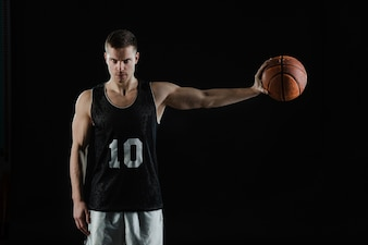 Basketball player grabbing the ball with his left hand