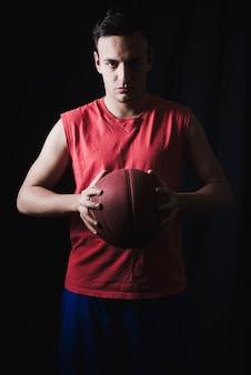 Basketball player posing on dark background