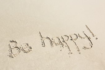 Be happy written on sand