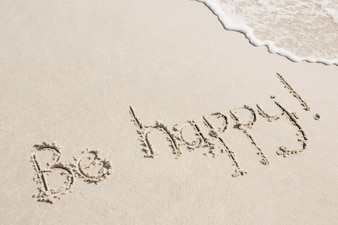 Be happy written on sand