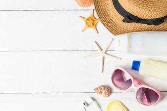 Beach accessories. Bag, towel, sunglasses and flip-flops on wooden background. Top view with copy space